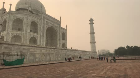 geliştirmek : Agra, India, November 10, 2019, Taj Mahal, tourists walk along the base of the mosque 4K