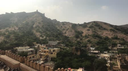 amer fort : Jaipur, India, November 05, 2019, Amer Fort, view from a window opening on tourists walking nearby 4K