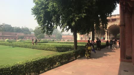Дели : Agra, India, November 10, 2019, Agra Fort, tourists stand in the shade of trees 4K