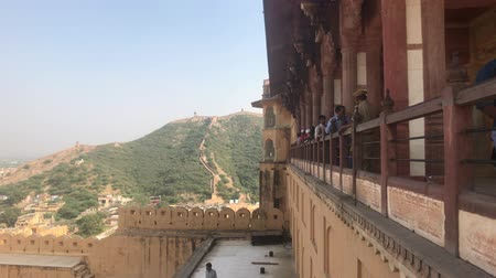amer fort : Jaipur, India, November 05, 2019, Amer Fort, tourists watch from the balcony of a fortress 4K