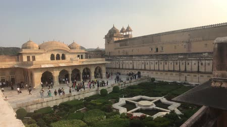 amer fort : Jaipur, India, November 05, 2019, Amer Fort tourists walk through the premises against the backdrop of green bushes part 3 4K