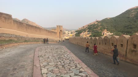 amer fort : Jaipur, India, November 05, 2019, Amer Fort tourists descend the old streets of the fort 4K