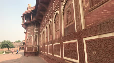 Дели : Agra, India, November 10, 2019, Agra Fort, tourists walk along the walls of the red brick structure 4K