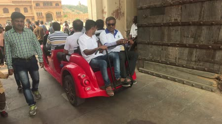 amer fort : Jaipur, India, November 05, 2019, Amer Fort, tourists drive a tiny car through the fortress part 2, 4K Stock Footage
