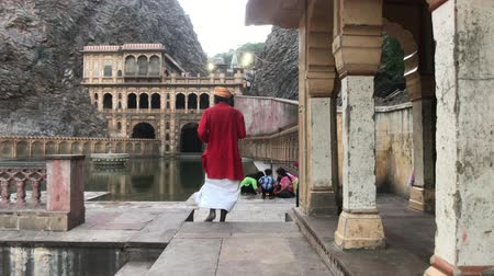 monkey temple : Jaipur, India, November 04, 2019 Galta Ji, a tourist walks against the backdrop of a small temple part 2 4K Stock Footage