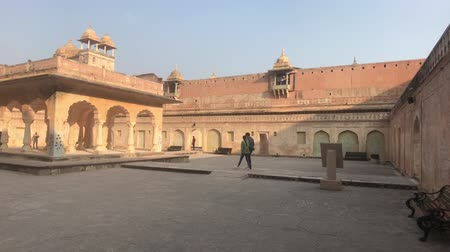 amer fort : Jaipur, India, November 05, 2019, Amer Fort a couple of tourists walk through the courtyard 4K
