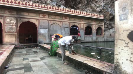 обряд : Jaipur, India, November 04, 2019 Galta Ji, tourists conduct a rite of abluising in the lake 4K