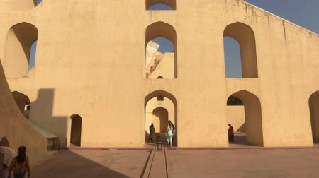 develop : Jaipur, India - November 04, 2019: Jantar Mantar tourists inspect historic buildings under the scorching sun part 5 4K