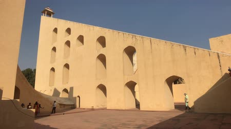 geliştirmek : Jaipur, India - November 04, 2019: Jantar Mantar tourists inspect historic buildings under the scorching sun part 7 4K Stok Video