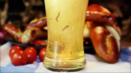 bavaria flag : Beer Pouring Into Glass With Waving German Flag and Bavarian White And Red Sausages With Mustard, Bavarian Buns and Pretzels At The Table In The Background. October Fest Concept