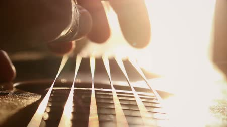 ladění : Guitarist Tuning and Checking Acoustic Guitar in Music Studio at Sunset
