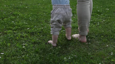 Little baby boy learns to walk on grass with mom Archivo de Video