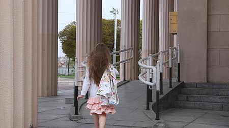 скат : Young girl walking up ramp at airport with pillars in background