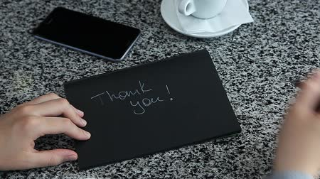 soletrar : Female hand spelling THANK YOU with marker on black craft sketch paper laying table