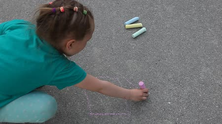 иллюстрировать : Child girl writes HOME with colored chalk on asphalt pavement close up outdoor
