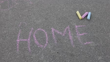 ilustrar : Word HOME spelled with colored chalk on asphalt pavement