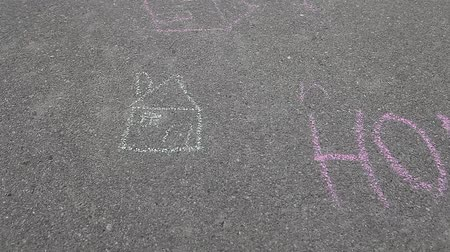 ilustrar : Drawn house next to word HOME spelled with colored chalk on asphalt pavement Vídeos