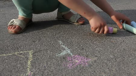 ilustrar : Child girl draws with colored chalk on asphalt pavement close up outdoor Stock Footage