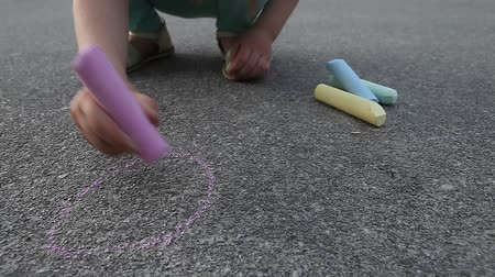ilustrar : Child girl draws with colored chalk on asphalt pavement close up outdoor Vídeos