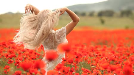 polního : Beautiful young blonde woman in red bright poppy field. Summer portrait