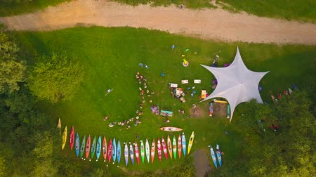 Aerial View. People, canoes, awning are on the shore of a lake or river