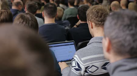 acadêmico : Rear view of a man using laptop at the conference Stock Footage