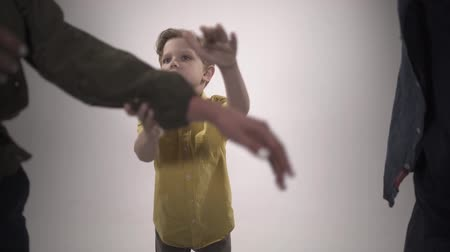 аргумент : The boy pulls the hand of his parents, who are cursing. Slow motion Стоковые видеозаписи