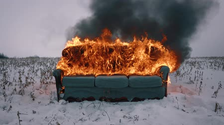 charred : A sofa burns in the winter field. The furniture is on fire. Concept video