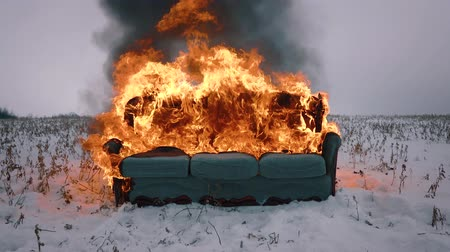 elpusztít : A sofa burns in the field. Conceptual video. Accelerated video Stock mozgókép