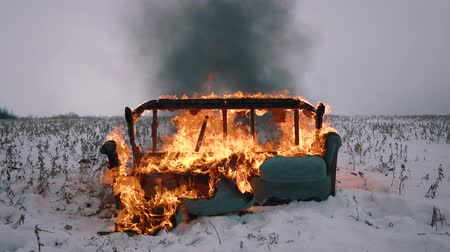 Fire destroyed the sofa. The sofa burns in the winter field