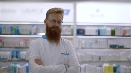 A doctor or pharmacist crosses his arms and looks sternly at the camera Stock Footage