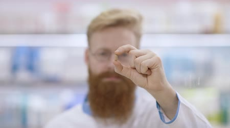 gyógyszerész : Healthcare concept. Young man with beard showing a pill to be taken Stock mozgókép