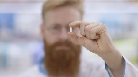 Young doctor or pharmacist shows a pill and nods his head approvingly