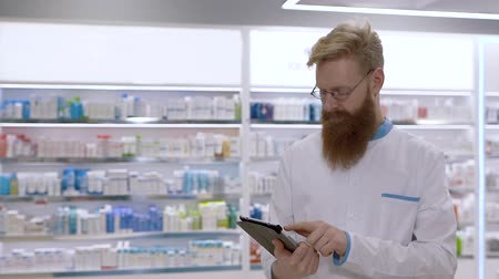 apotheker : A young pharmacist looks at the tablet and then nods his head approvingly