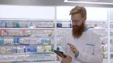 A young doctor or pharmacist uses a tablet and then nods disapprovingly