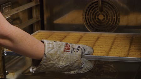 get out : The cook takes out a baking tray with a rectangular cookie from a professional cooking oven.