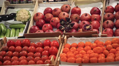 persimmons : Pomegranates,persimmons and tangerines on the shelves in stores