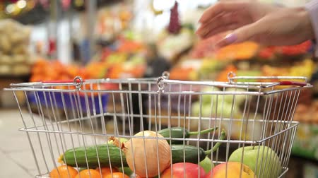 add to cart : Shopping cart with vegetables on the background of the market Stock Footage