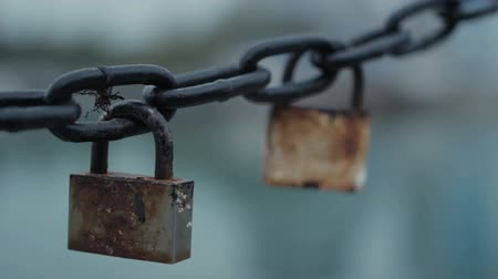 цепь : Two old lock hanging on the anchor chain. Chain with locks swinging. Change the camera focus when you zoom.