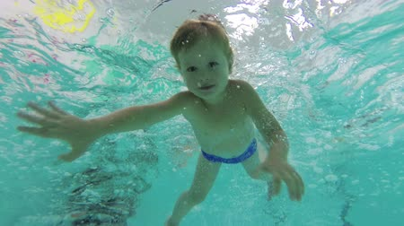 A little boy dives into the pool, swims underwater with her eyes. The view from below. 4K, 25fps Wideo