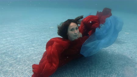 The teenage girl swims and plays with a red and blue cloth underwater at the bottom of the pool. Action camera. 4K. 29.97 fps