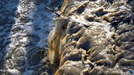 waste water : Dirty waste is drained into a stormy river. Close-up, high detail. 4K, 25 fps.