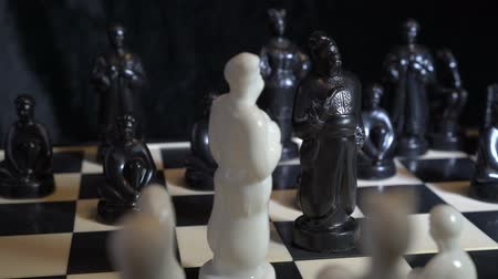 šachy : Chess pieces in the form of Slavic Cossacks stand on a chessboard on a dark background. Close-up, high detail. Rotation. 4K, 25 fps.