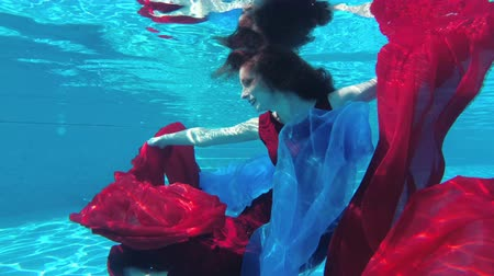 sereia : A girl swims in her red dress. Slow motion. Raw video. 4K. 25 fps. Stock Footage