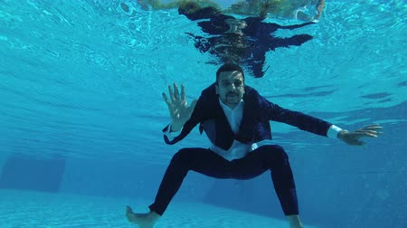 The groom in a suit swims and poses under the water in the pool. He looks at the camera, waves his hands and smiles. Slow motion. Action camera underwater. 4K, 25 fps Wideo