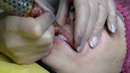 Extreme close-up of the procedure of permanent lip makeup a young girl in a beauty salon. The view from the top. 4K. 25 fps.