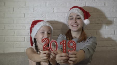 Two sisters, a little girl and a teenager, in Santas hats holding red figures 2019, play them and smile sitting on the couch on a white background. Shift focus from faces to numbers. 4K. 25 fps.