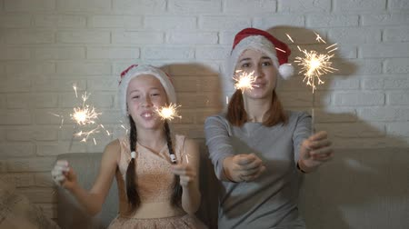 Two sisters, a little girl and a teenager, in Santas hats holding lighted sparklers in their hands, wave them and smile sitting on the couch on a white background. Close up. 4K. 25 fps Filmati Stock