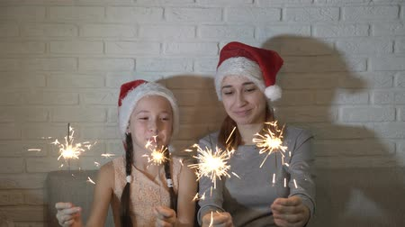 Cheerful, happy children in Santas hats hold lighted sparklers in their hands, wave them and smile sitting on a sofa against a white brick wall. Close up. 4K. 25 fps.