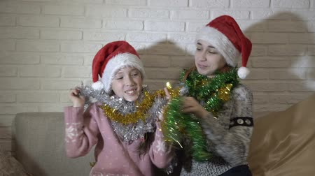 Cheerful, happy little girls in red hats of Santa Claus play with each other tinsel, laugh and smile sitting on the couch against a white brick wall. Close up. 4K. 25 fps
